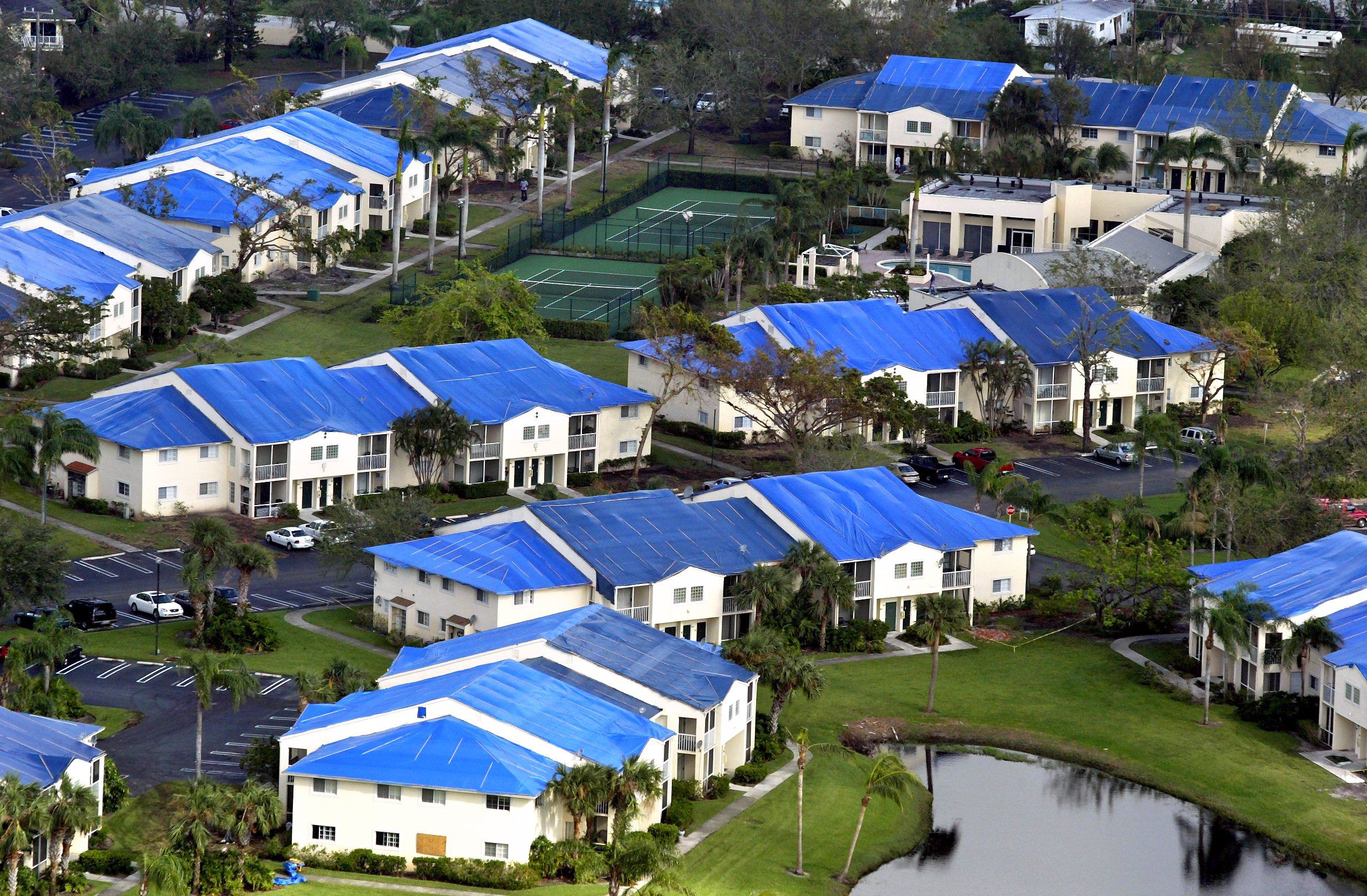Group of houses with blue tarps on them