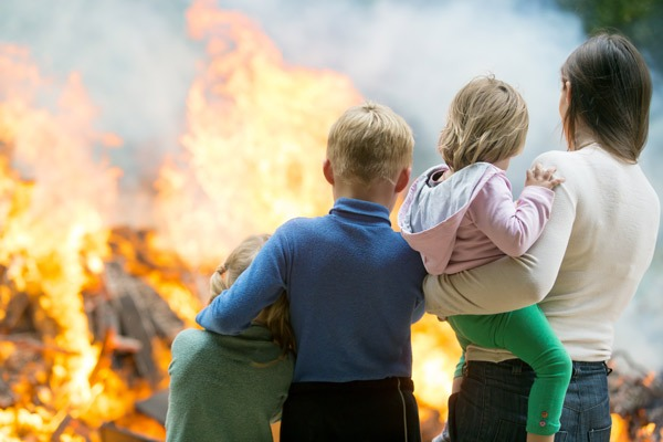 Family with kids in front of a house fire